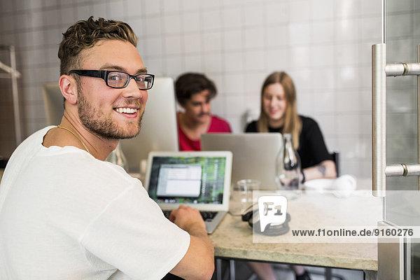 Porträt eines glücklichen jungen Geschäftsmannes mit Kollegen im Hintergrund im Kreativbüro