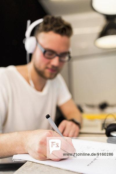 Jungunternehmer beim Schreiben auf Buch im Kreativbüro