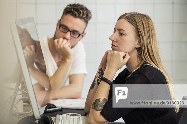 Junger Geschäftsmann und Geschäftsfrau beim Blick auf den Computermonitor im Kreativbüro
