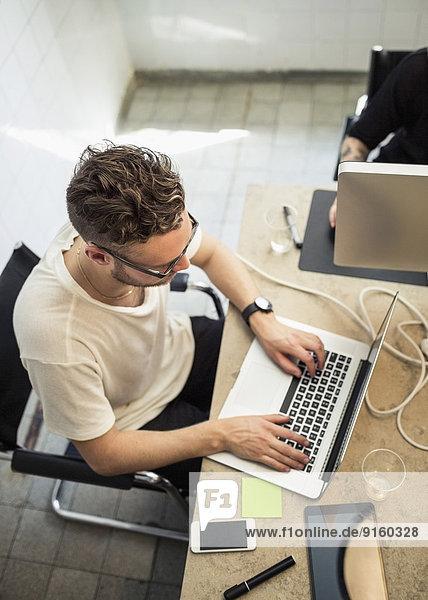 Hochwinkelansicht eines jungen Geschäftsmannes mit Laptop im Kreativbüro