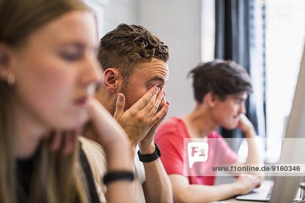 Müde junge Geschäftsleute reiben sich die Augen mit Kollegen  die in einem neuen Büro arbeiten.