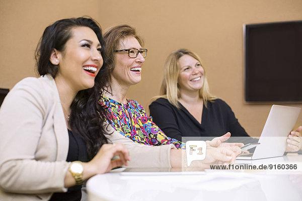 Glückliche Geschäftsfrauen in der Besprechung im Vorstandszimmer im Kreativbüro