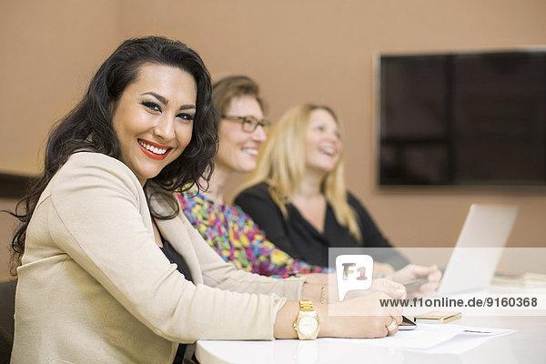 Porträt einer glücklichen Geschäftsfrau mit Kollegen am Konferenztisch im Kreativbüro
