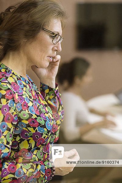 Side view of businesswoman using mobile phone in creative office