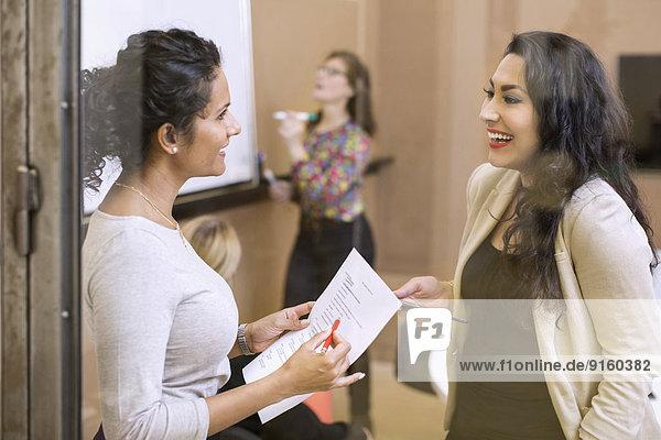 Happy businesswomen conversing in board room at office
