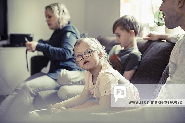 Porträt eines behinderten Mädchens  das mit seiner Familie auf dem Sofa sitzt.