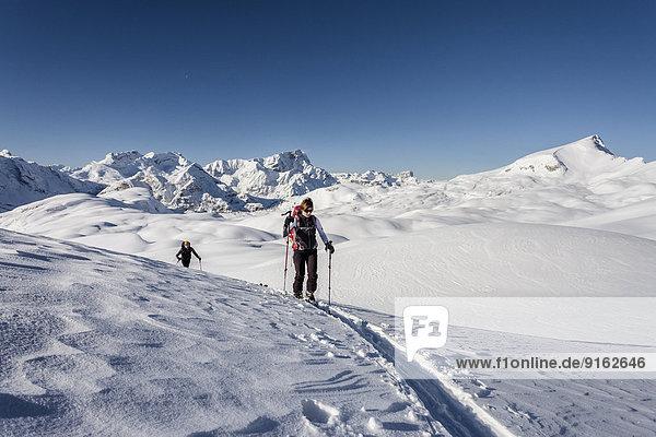 Skitourengeher beim Aufstieg auf den Seekofel im Naturpark Fanes-Sennes-Prags in den Dolomiten  hinten das Fanesgebiet mit Piz de Lavarela  Conturines  Piz de Sant Antone und Neuner  rechts die Seneser Karspitze  St. Vigil  Gadertal  Südtirol  Italien