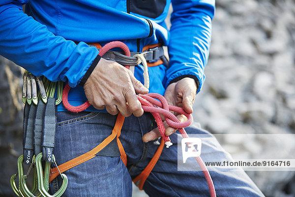 Kletterer befestigt einen geschlagenen Achterknoten an seinem Kletterseil  Klettergebiet Martinswand  Zirl  Tirol  Österreich