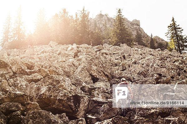 Man climbing rocky hillside