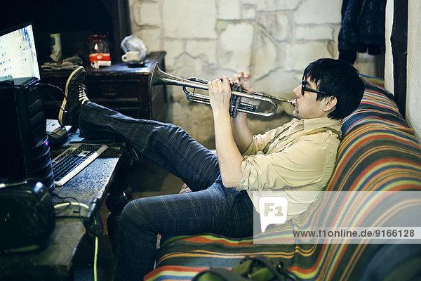 Mari man playing trumpet on sofa