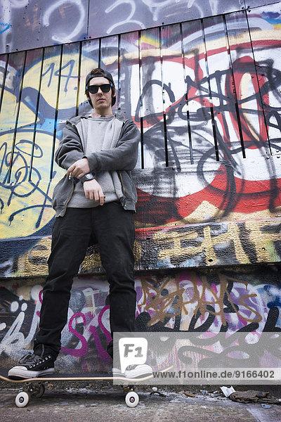 Caucasian teenage boy on skateboard by graffiti wall