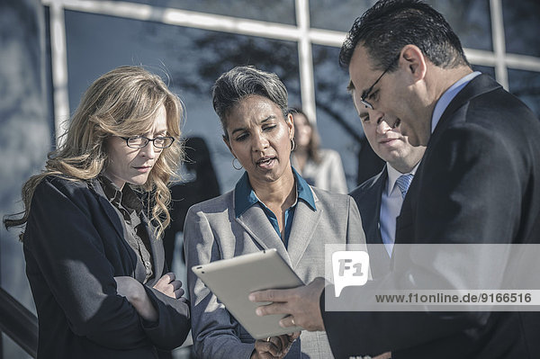 Business people using digital tablet outside office