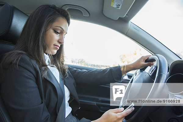 Mixed race businesswoman using cell phone while driving