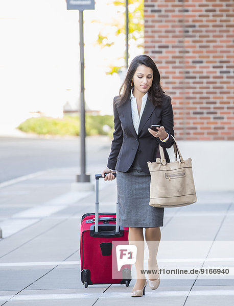 Mixed race businesswoman with suitcase on sidewalk