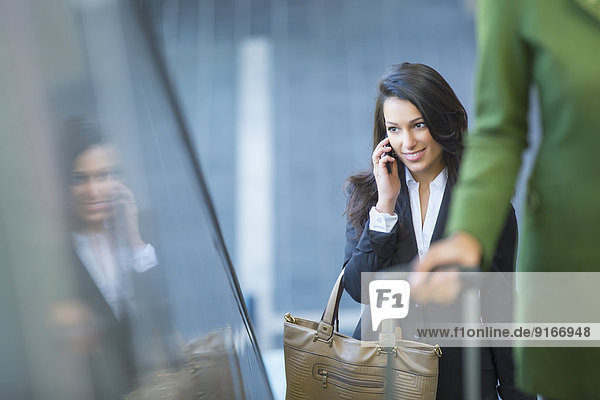 Mixed race businesswoman talking on cell phone on escalator