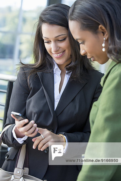 Businesswomen using cell phone outdoors