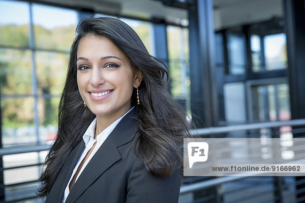 Mixed race businesswoman smiling outdoors