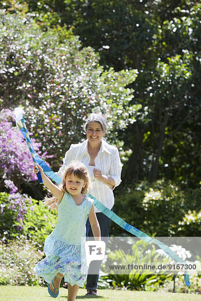 Grandmother and granddaughter playing in garden