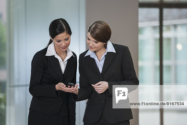 Businesswomen using cell phone in office