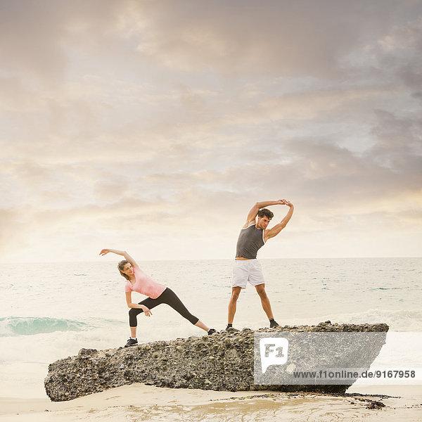 Caucasian runners stretching on beach