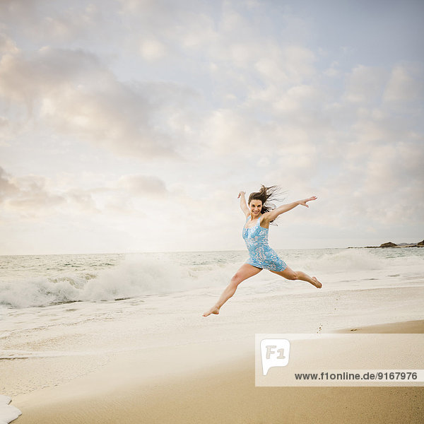 Caucasian woman jumping on beach