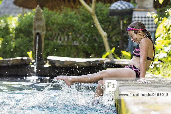 Caucasian girl splashing in swimming pool