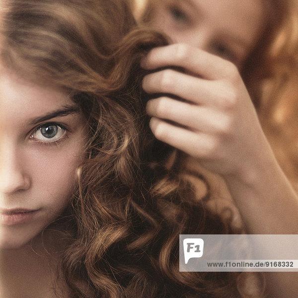 Caucasian girl braiding friend's hair