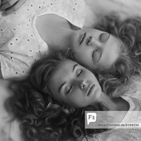 Caucasian girls sleeping on bed together Caucasian girls sleeping on bed together