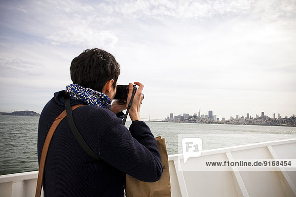 Woman taking picture of city skyline  San Francisco  California  United States