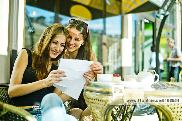 Women reading map together at sidewalk cafe