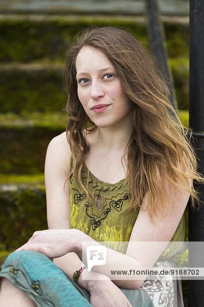 Caucasian teenage girl sitting on steps outdoors