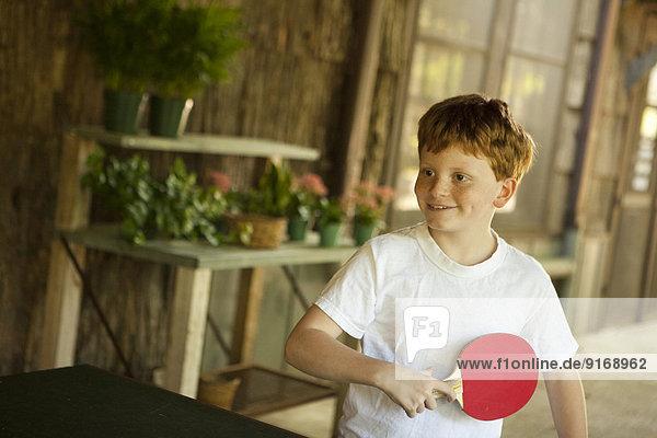 Caucasian boy playing table tennis