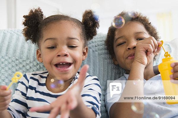 Black children blowing bubbles together