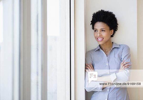 Black businesswoman smiling by window