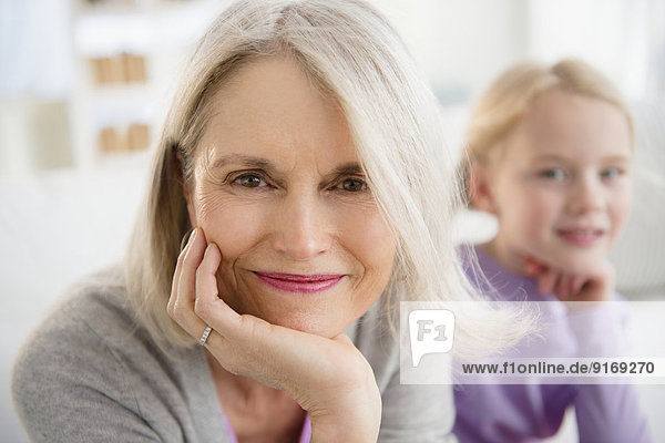 Senior Caucasian woman sitting with granddaughter
