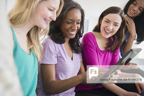 Women using digital tablet together