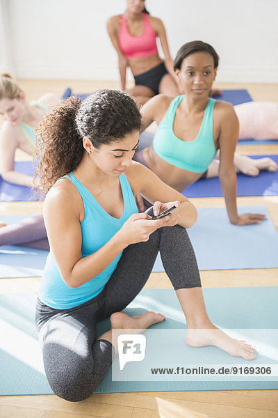 Woman texting in yoga class