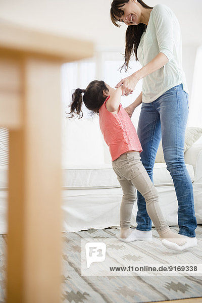 Hispanic mother and daughter dancing together