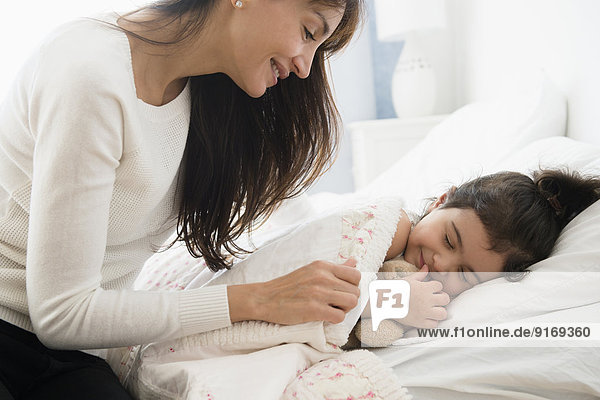 Hispanic mother tucking daughter into bed