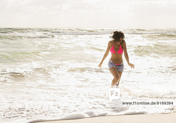 African American woman playing in waves on beach