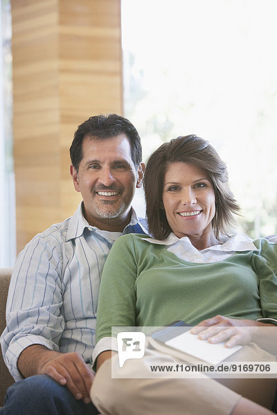 Hispanic couple relaxing on sofa