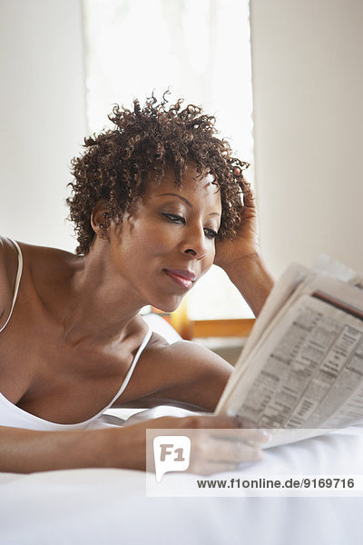 African American woman reading in bed