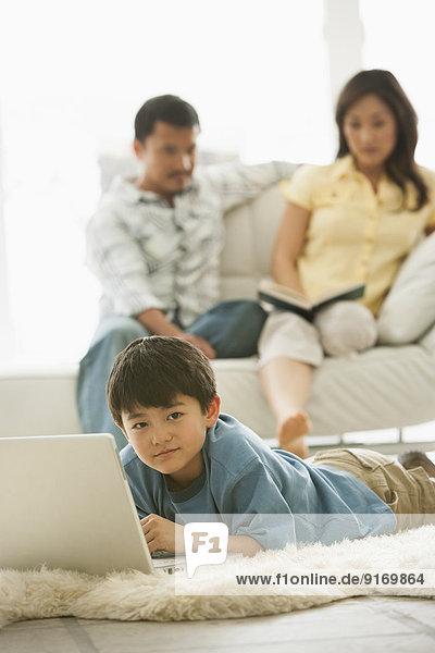 Boy using laptop in living room
