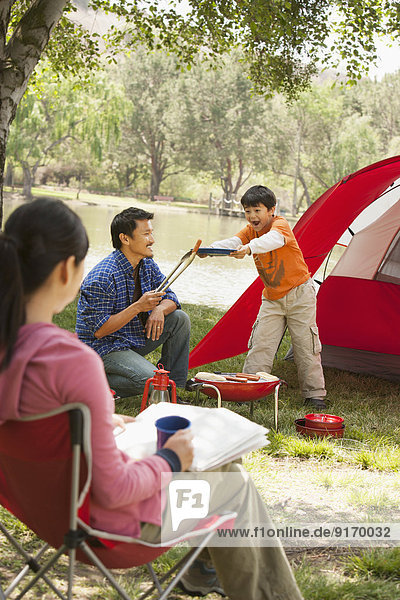 Asian family relaxing at campsite