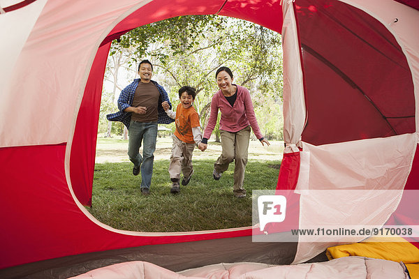 Asian family running to tent at campsite