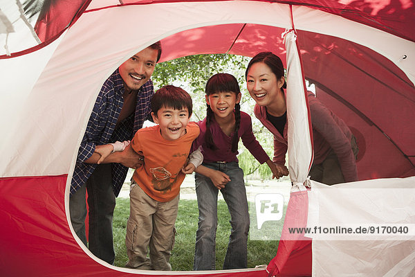 Family peering in tent at campsite