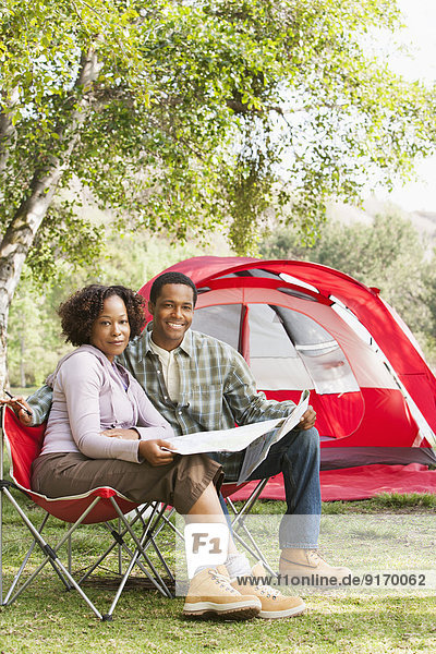 Couple reading newspaper together at campsite