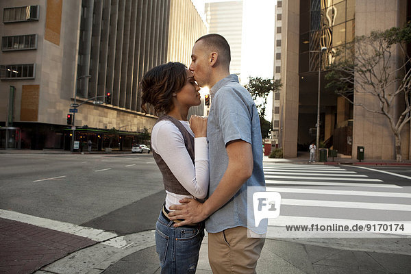 Couple kissing on city street