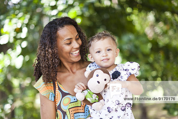 Mother holding toddler outdoors