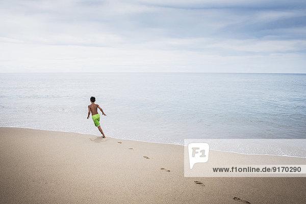 Mixed race boy playing on beach Mixed race boy playing on beach